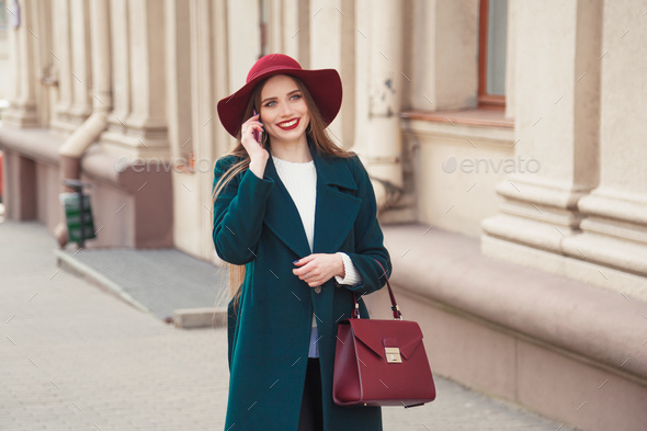 Beautiful stylishly dressed young woman smiling while talking on the phone outdoors. - Stock Photo - Images