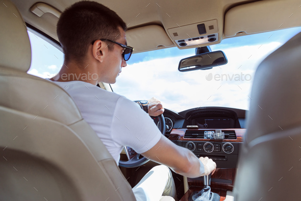 Young stylish man in sunglasses driving a car. View from the back, with the rear passenger seat. - Stock Photo - Images
