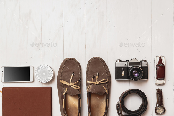 Set of men's blogger accessories for the traveler on a white wooden background. - Stock Photo - Images