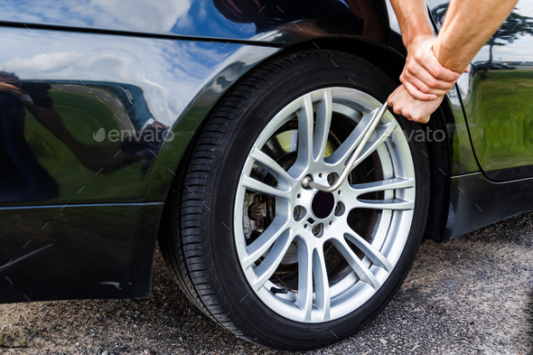 man unscrews bolts of the rear wheel the car to change the tires. - Stock Photo - Images