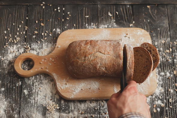 Man hand slicing home-made bread - Stock Photo - Images