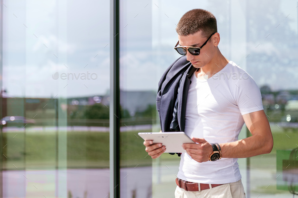 Young fashionable wearing a freelancer working on the tablet - Stock Photo - Images