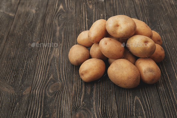 Handful of Raw harvested potatoes on dark wooden background. - Stock Photo - Images