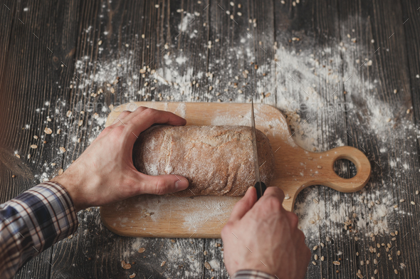 man in plaid shirt with knife cut home-baked bread on wooden board - Stock Photo - Images