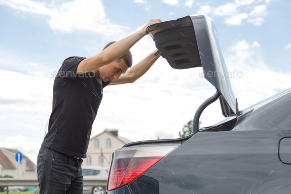 Car broke down on the way. The man opened the trunk to take the tools. - Stock Photo - Images