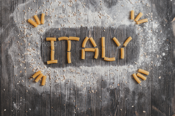 Lettering ITALY pasta on black rustic wooden background. Top view - Stock Photo - Images