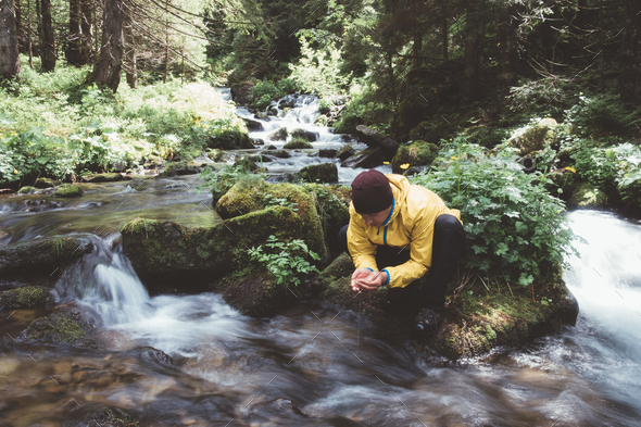 Man drink water from clear mountain stream - Stock Photo - Images