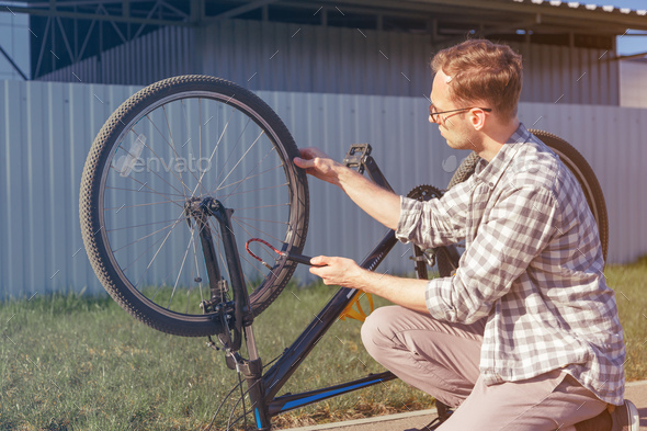Man uses a bicycle pump. Cyclist repairs bike in trip. - Stock Photo - Images
