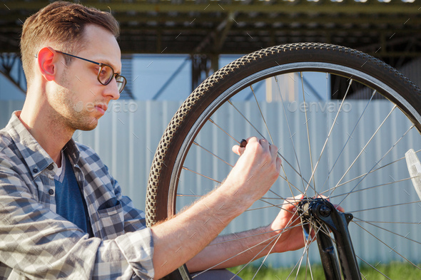 The mechanic man repair wheel of the bicycle. outdoor - Stock Photo - Images