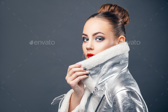 Young woman wearing futuristic silver fashionly jacket. - Stock Photo - Images