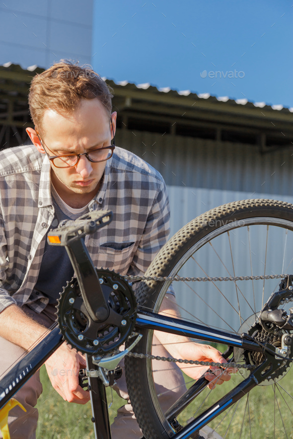 Young handsome man is tuning the bike chain. - Stock Photo - Images