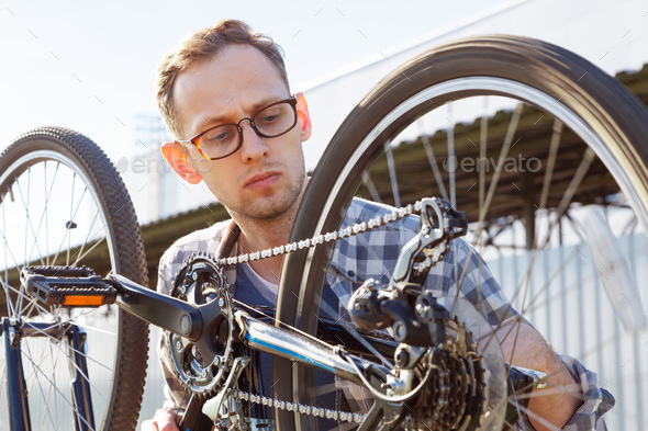 The mechanic man checks transmission system of the bicycle outdoor. - Stock Photo - Images