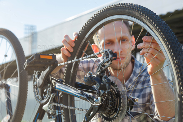 A young male engineer master is looking at a bicycle wheel - Stock Photo - Images