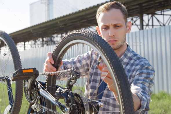 A concentrated craftsman is diagnosing bike malfunctions on the street. - Stock Photo - Images