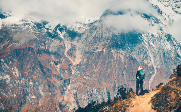 Woman with backpack on the path and mountains - Stock Photo - Images