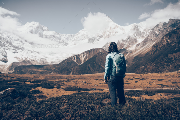 Standing young woman with backpack and mountains - Stock Photo - Images