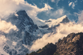 Mountains with snowy peaks in clouds at sunset - PhotoDune Item for Sale