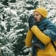 Man in Yellow Winter Jacket Cleans His Hands From Snow Standing in the Mountain Forest - VideoHive Item for Sale