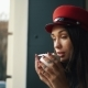 Charming Woman in Red Hat Drinks Coffee Sitting in the Cosy Cafe - VideoHive Item for Sale