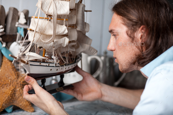 young man looks at model of sailing ship in vintage interior - Stock Photo - Images