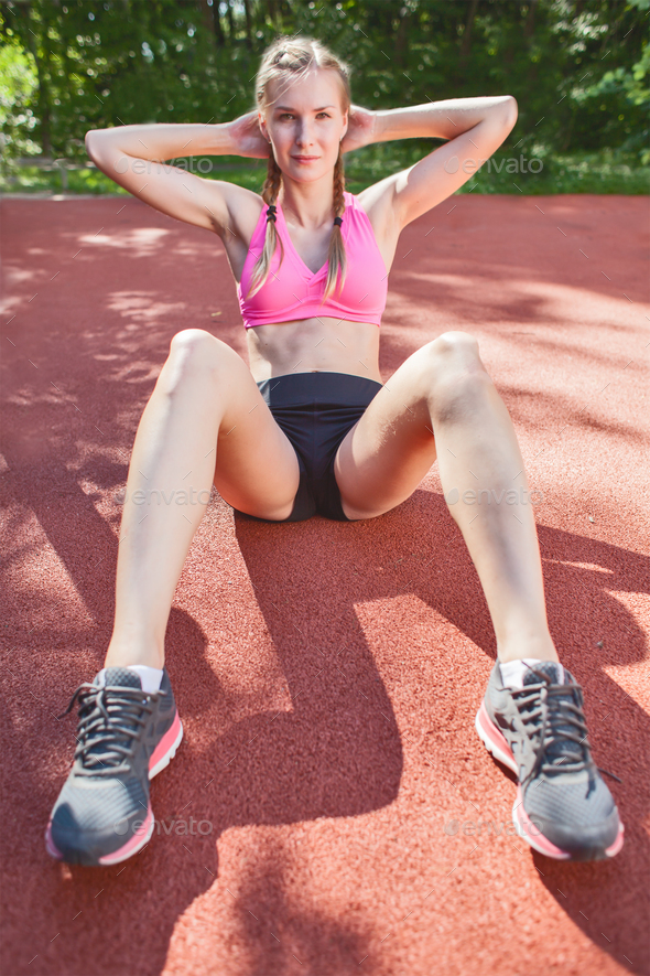 young smiling sportswoman in sportswear doing abs exercise - Stock Photo - Images