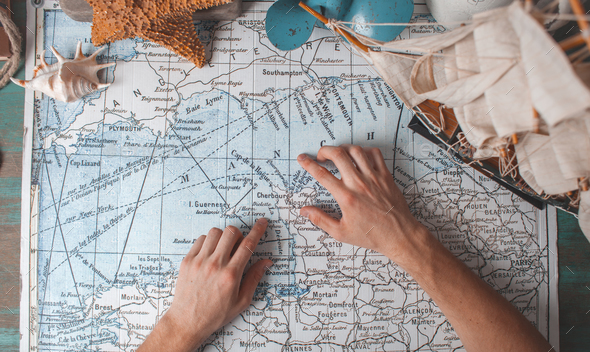 man's hand on map on desk with traveller attributes - Stock Photo - Images
