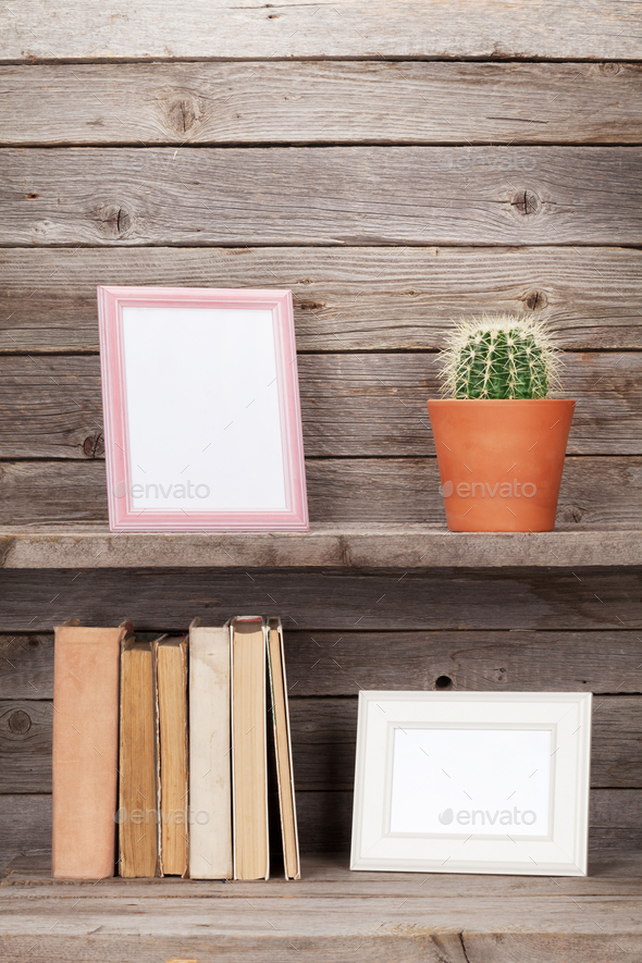 Old books and photo frames on a wooden shelf - Stock Photo - Images