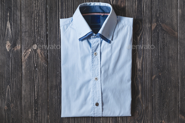Men's classic blue folded cotton shirt with long or short sleeve on black brutal background. - Stock Photo - Images