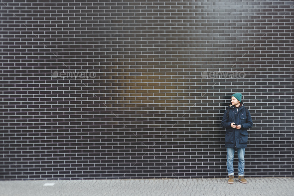 Young stylishly dressed man in winter clothes standing on a blank wall of black tiles. - Stock Photo - Images