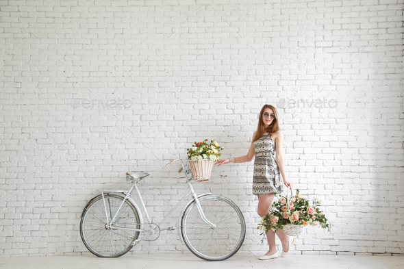 Portrait of a happy beautiful young girl with vintage bicycle and flowers - Stock Photo - Images