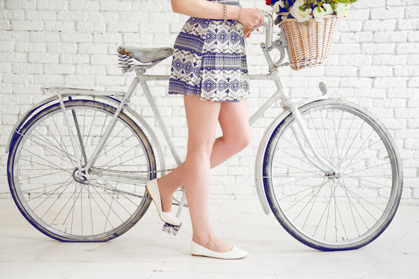 Woman bare feet near the white bicycle in spring - Stock Photo - Images