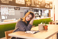 Young woman freelancer sitting in cafe after hard work day - PhotoDune Item for Sale