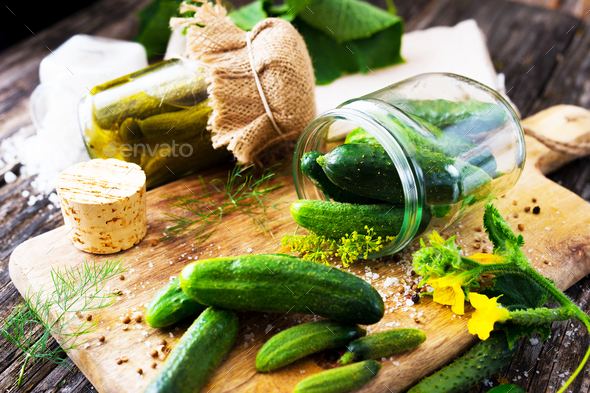 Jars of pickled marinated cucumbers on rustic table - Stock Photo - Images