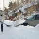 Young Woman Cleans Snow by Shovel for Car in Suburbs in Winter - VideoHive Item for Sale