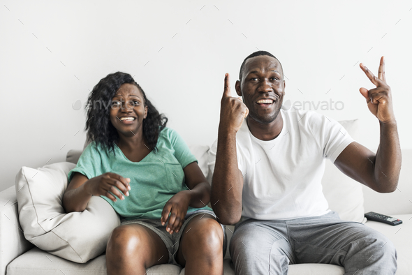 Black couple watching movie together at home - Stock Photo - Images
