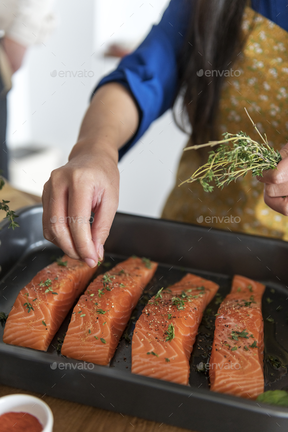 Woman adding spices and herb to raw salmon - Stock Photo - Images