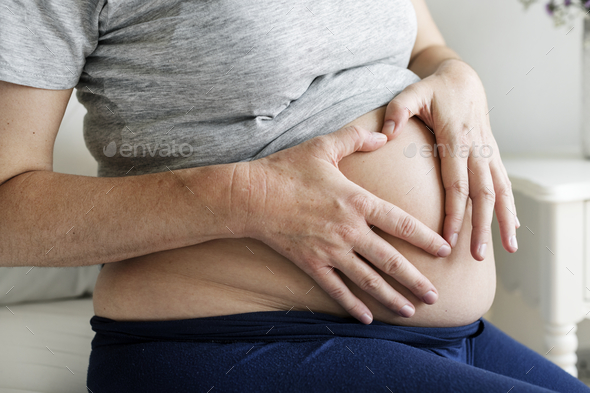 Pregnant woman sitting on the bed - Stock Photo - Images