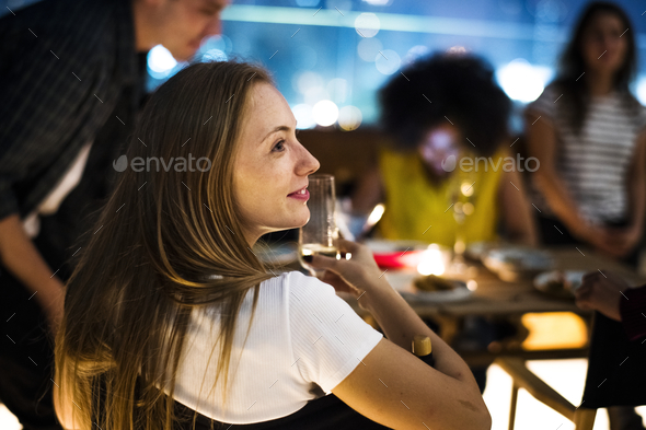 Young adults dinner night with friends at a rooftop restaurant - Stock Photo - Images