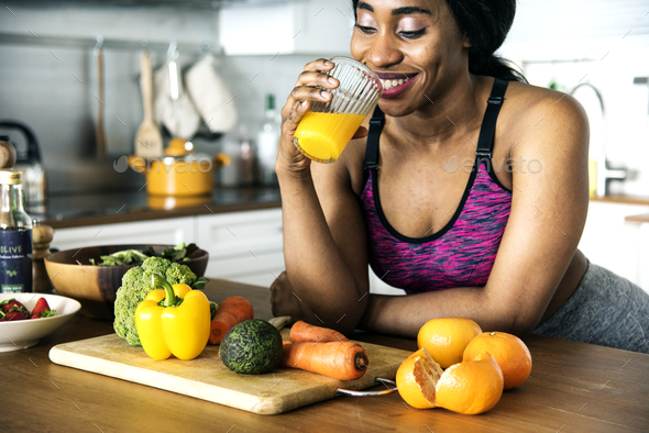 Black woman is drinking orange juice - Stock Photo - Images