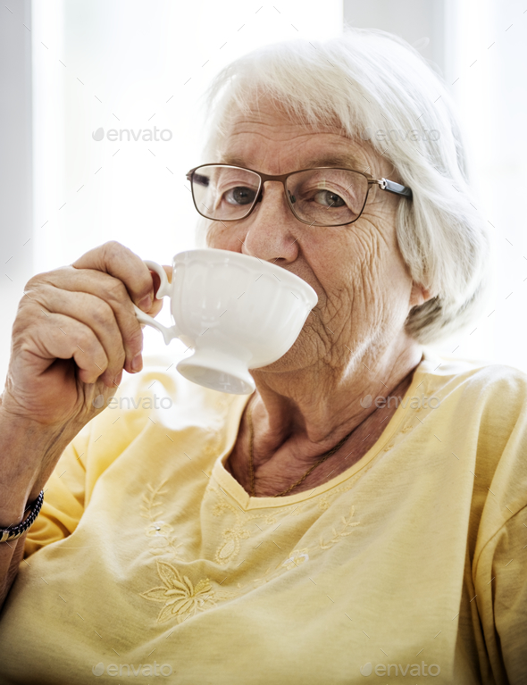 Senior woman sipping tea while looking at the camera - Stock Photo - Images