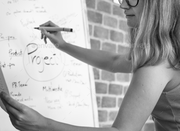 Caucasian woman writing project plan on white board - Stock Photo - Images
