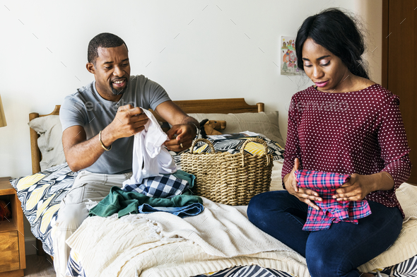 Black couple folding clothes together - Stock Photo - Images