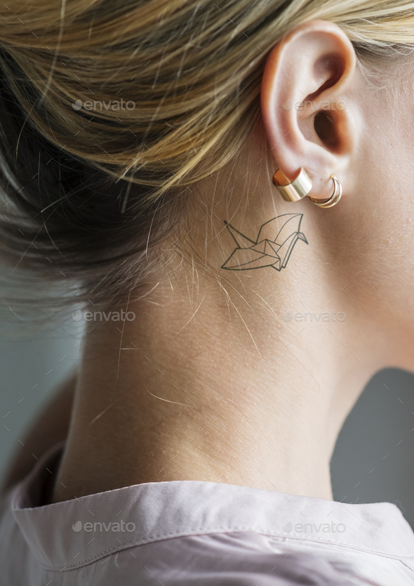 Closeup of a simple behind the ear tattoo of a young woman - Stock Photo - Images