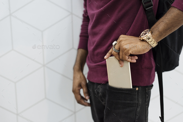 African man putting mobile phone on his pocket - Stock Photo - Images