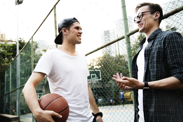 Young adult male friends playing basketball in the park - Stock Photo - Images