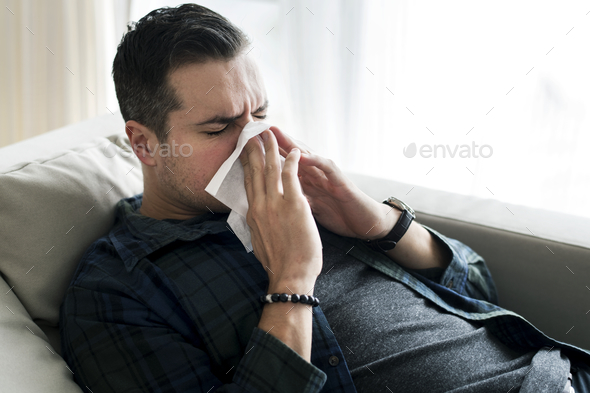 A sneezing Caucasian man on sofa - Stock Photo - Images