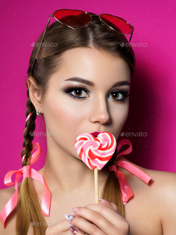 Young beautiful woman holds heart shaped lollipop - Stock Photo - Images