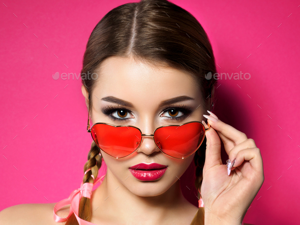 Young woman looks over heart shaped glasses - Stock Photo - Images