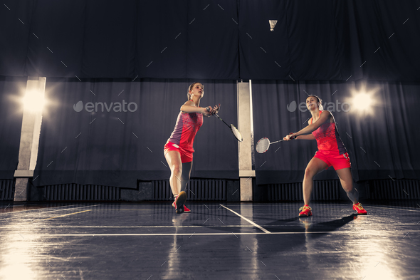 Young women playing badminton at gym - Stock Photo - Images