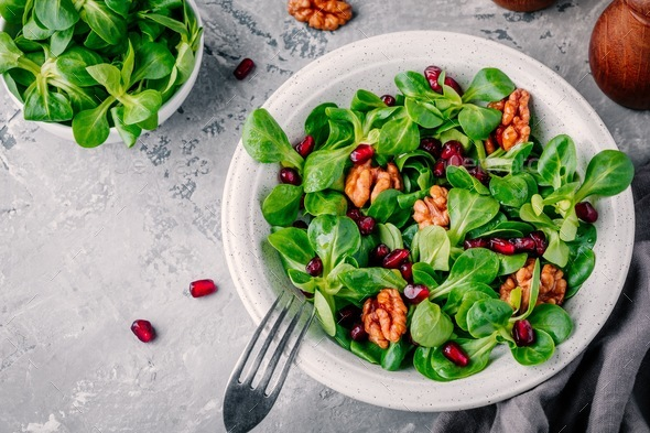 Green lettuce salad with walnuts and pomegranate seeds - Stock Photo - Images